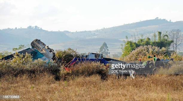 This photo taken on December 26 2012 shows officials at the scene where an Air Bagan plane crashlanded the day before near Heho airport in Myanmar's...