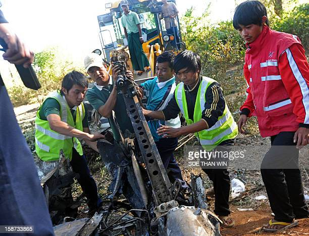 This photo taken on December 26 2012 shows officials moving debris at the scene where an Air Bagan plane crashlanded the day before near Heho airport...