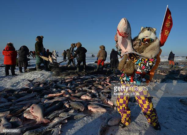 This photo taken on December 28, 2013 shows Chinese tourists who come to buy fish from members of the Chinese Mongolian ethnic group who catch fish...
