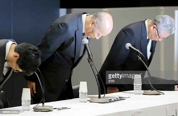This photo taken on December 28 2016 shows Tadashi Ishii president of Japan's biggest advertising agency Dentsu bowing with other excutives during a...