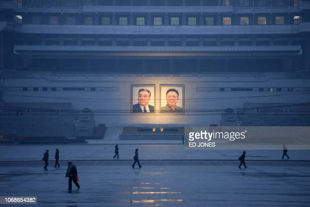 TOPSHOT This photo taken on December 3 2018 shows pedestrians walking past the portraits of late North Korean leaders Kim Il Sung and Kim Jong Il...