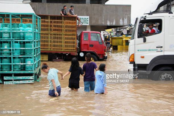 This photo taken on December 30 2018 shows people walking through a flooded street in the town of Baao in Camarines Sur province The death toll from...