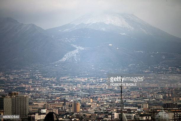 This photo taken on December 31 2014 shows a general view of Naples under cloudy skies as the snowcovered Vesuvius volcano looms in the background...
