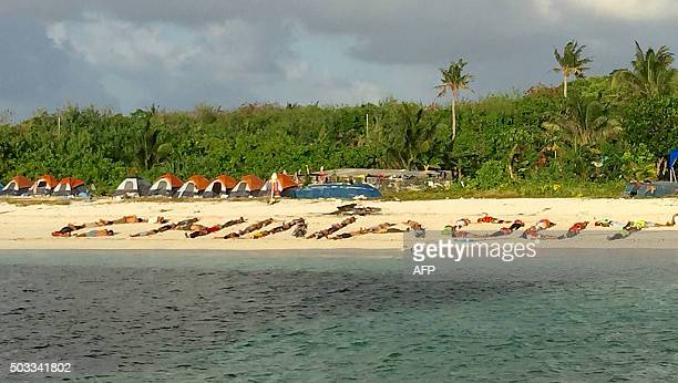 This photo taken on December 31 shows Filipino children forming a sign 'China Out' during a protest on a beach at Pagasa island a remote...