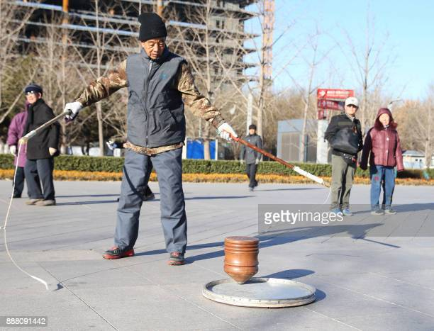 This photo taken on December 4 2017 shows a man exercising with a spinning top which weighs 354 kilogrammes at the Olympic Forest Park in Beijing /...