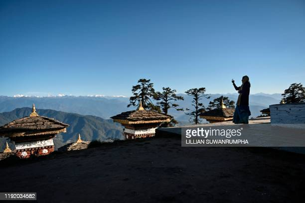 """This photo taken on December 6, 2019 shows a tourist taking pictures of the """"Druk Wangyal Chortens"""" stupas, with the Bhutanese Himalayas in the..."""
