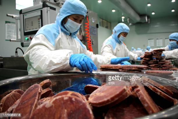 This photo taken on December 6, 2020 shows workers packaging frozen steak for export at a beef processing plant in Binzhou, in eastern China's...