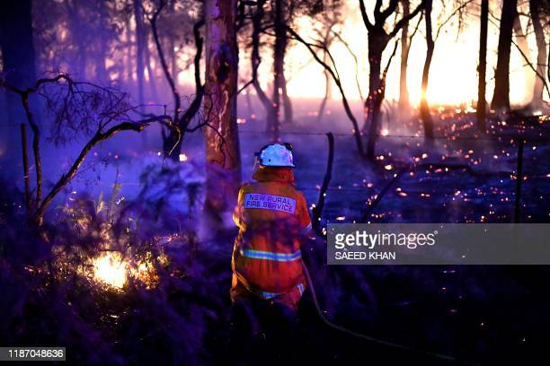 TOPSHOT This photo taken on December 7 2019 shows a firefighter conducting back burning measures to secure residential areas from encroaching...