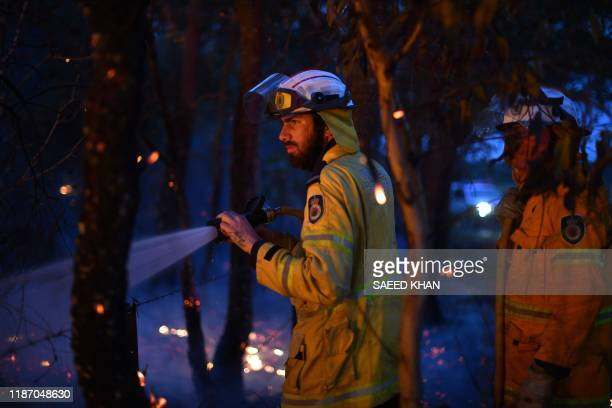 This photo taken on December 7 2019 shows firefighters conducting back burning measures to secure residential areas from encroaching bushfires at the...