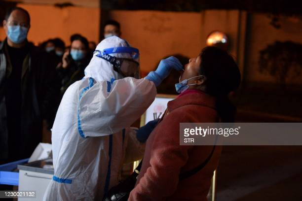 This photo taken on December 8, 2020 shows a health worker conducting a nucleic acid test on a resident in Chengdu, in western China's Sichuan...