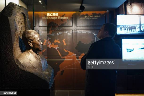 This photo taken on December 8, 2020 shows a man standing next to a statue of Ho Feng-Shan , a Chinese diplomat in Vienna who saved thousands of Jews...
