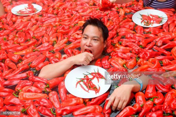 This photo taken on December 9 2018 shows a competitor taking part in a chilli pepper eating contest in a hot spring filled with chilli peppers in...