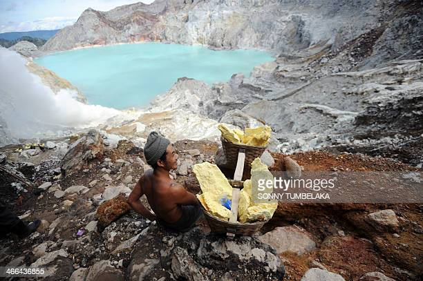 This Photo taken on February 1 2014 shows a miner carrying blocks of sulphur from Ijen crater in Banyuwangi East Java A miner can weigh from 45 to...