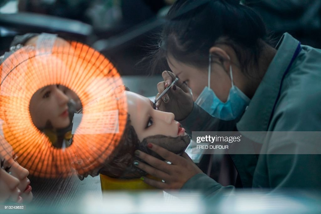 This photo taken on February 1, 2018 shows a worker painting the face of a silicone doll at a factory of EXDOLL, a firm based in the northeastern Chinese port city of Dalian. With China facing a massive gender gap and a greying population, a company wants to hook up lonely men and retirees with a new kind of companion: 'Smart' sex dolls that can talk, play music and turn on dishwashers. / AFP PHOTO / FRED DUFOUR / TO GO WITH China-sex-lifestyle, FOCUS by Joanna CHIU