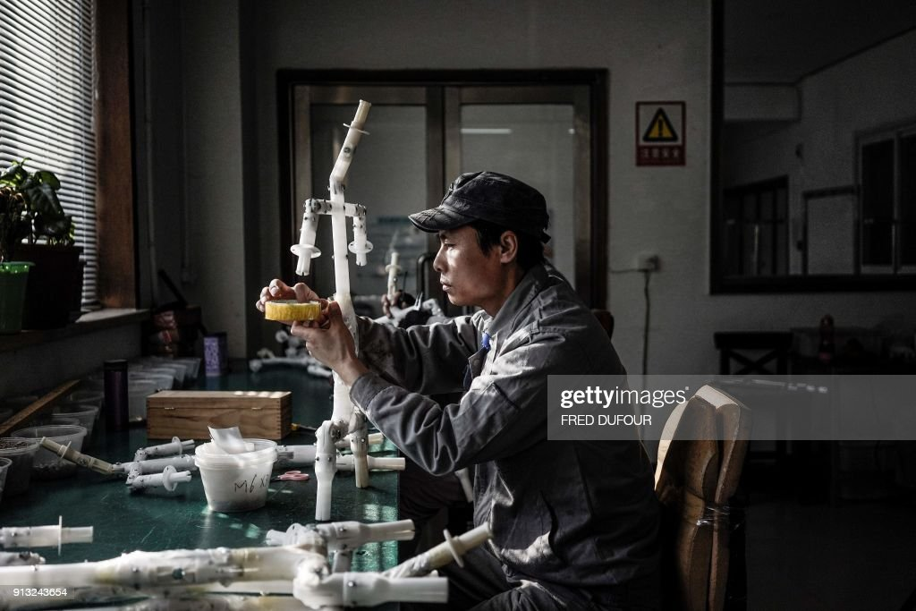 This photo taken on February 1, 2018 shows a worker setting up the framework for silicone dolls at a doll factory of EXDOLL, a firm based in the northeastern Chinese port city of Dalian. With China facing a massive gender gap and a greying population, a company wants to hook up lonely men and retirees with a new kind of companion: 'Smart' sex dolls that can talk, play music and turn on dishwashers. / AFP PHOTO / FRED DUFOUR / TO GO WITH China-sex-lifestyle, FOCUS by Joanna CHIU