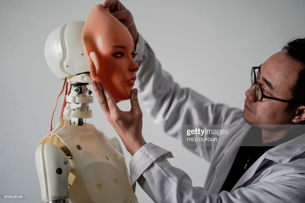 TOPSHOT - This photo taken on February 1, 2018 shows an engineer holding a silicon face against the head of a robot at a lab of a doll factory of EXDOLL, a firm based in the northeastern Chinese port city of Dalian. With China facing a massive gender gap and a greying population, a company wants to hook up lonely men and retirees with a new kind of companion: 'Smart' sex dolls that can talk, play music and turn on dishwashers. / AFP PHOTO / FRED DUFOUR / TO GO WITH China-sex-lifestyle, FOCUS by Joanna CHIU