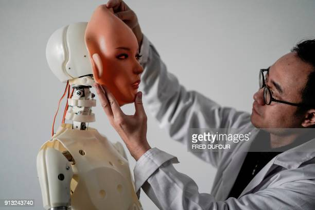 TOPSHOT This photo taken on February 1 2018 shows an engineer holding a silicon face against the head of a robot at a lab of a doll factory of EXDOLL...