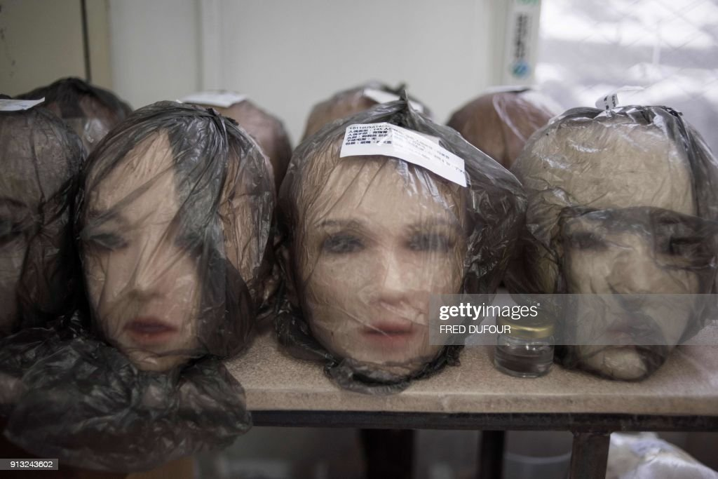 This photo taken on February 1, 2018 shows non-robotic silicone doll heads at a doll factory of EXDOLL, a firm based in the northeastern Chinese port city of Dalian. With China facing a massive gender gap and a greying population, a company wants to hook up lonely men and retirees with a new kind of companion: 'Smart' sex dolls that can talk, play music and turn on dishwashers. / AFP PHOTO / FRED DUFOUR / TO GO WITH China-sex-lifestyle, FOCUS by Joanna CHIU