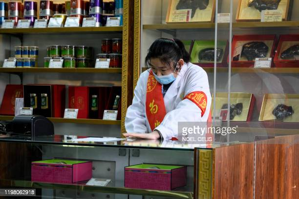 This photo taken on February 1 2020 shows an employee wearing a protective face mask at a traditional Chinese medicine store in Beijing A claim by...
