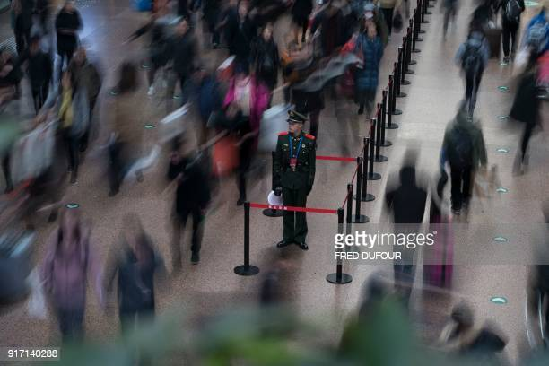 TOPSHOT This photo taken on February 10 2018 shows a Chinese soldier standing in the main hall while travellers rush before boarding trains at the...