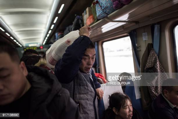 This photo taken on February 10 2018 shows a passenger trying to make his way through a crowded train as it leaves Beijing for the 26hour journey to...