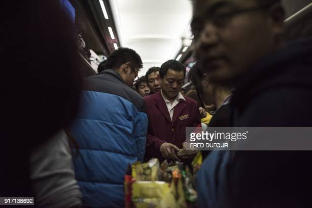 This photo taken on February 10 2018 shows a waiter trying to make his way through passengers on a crowded car during a 26hour train journey from...