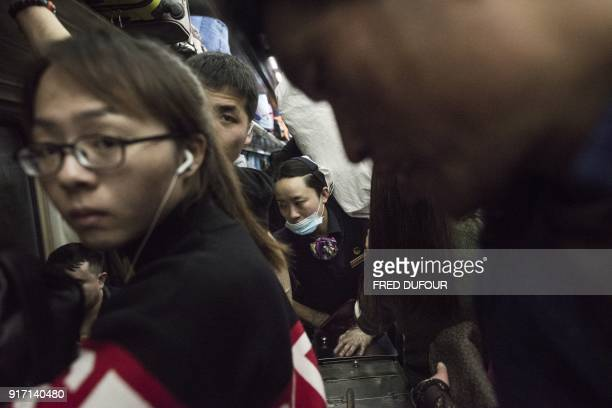 This photo taken on February 10 2018 shows a waitress trying to make her way through passengers on a crowded car during a 26hour journey from Beijing...