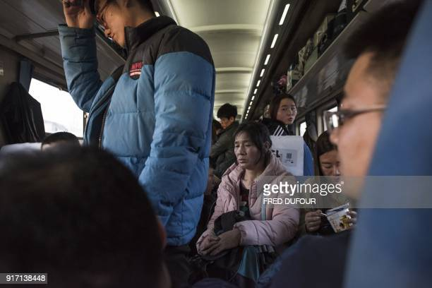 This photo taken on February 10 2018 shows passengers sitting in a crowded train as it leaves the West Railway Station in Beijing for the 26hour...