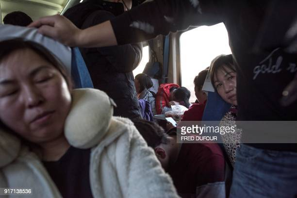 This photo taken on February 10 2018 shows passengers sitting on a crowded train after it left Beijing for the 26hour journey to Chengdu ahead of the...