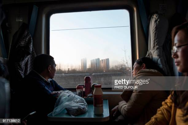 TOPSHOT This photo taken on February 10 2018 shows passengers sitting on a crowded train as it leaves Beijing for the 26hour journey to Chengdu ahead...