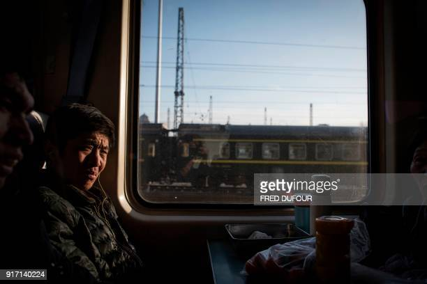 This photo taken on February 10 2018 shows passengers sitting on a crowded train as it leaves Beijing for the 26hour journey to Chengdu ahead of the...