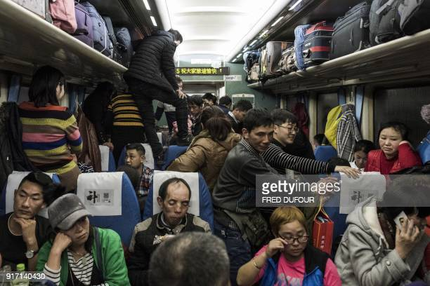 TOPSHOT This photo taken on February 10 2018 shows passengers travelling on a crowded train during the 26hour journey from Beijing to Chengdu in...