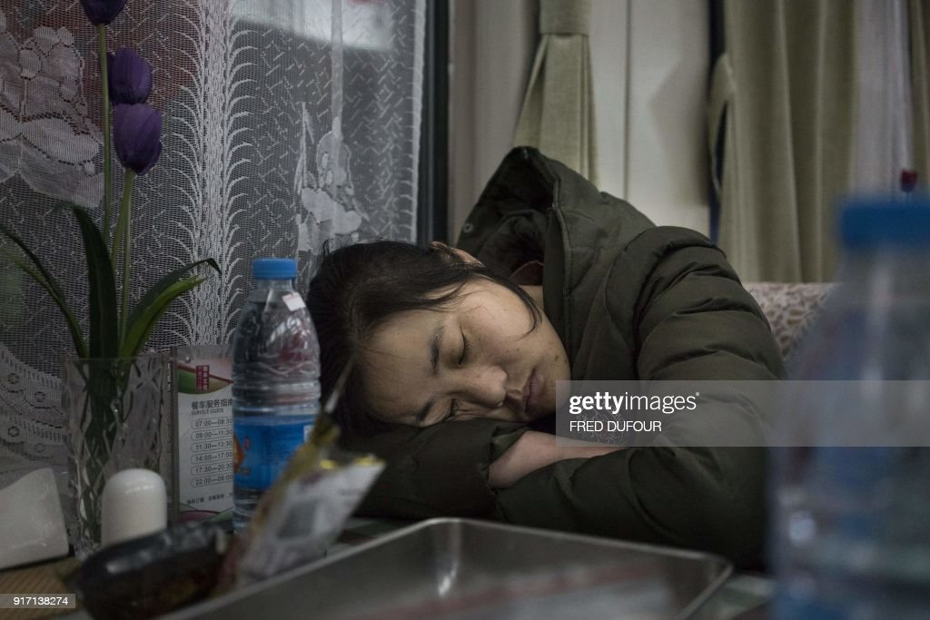 This photo taken on February 10, 2018 shows people sleeping in the restaurant car during the 26-hour train journey from Beijing to Chengdu, in Taiyuan, as travellers head home from the capital ahead of the Lunar New Year. China is in the midst of its annual travel rush as millions head to their hometowns to enjoy a week-long holiday. The Lunar New Year begins on February 16, and authorities expect more than 390 million train trips to take place between February 1 and March 12. / AFP PHOTO / FRED DUFOUR / TO GO WITH China-NewYear-migration-transport,FOCUS by Joanna Chiu and Fred Dufour