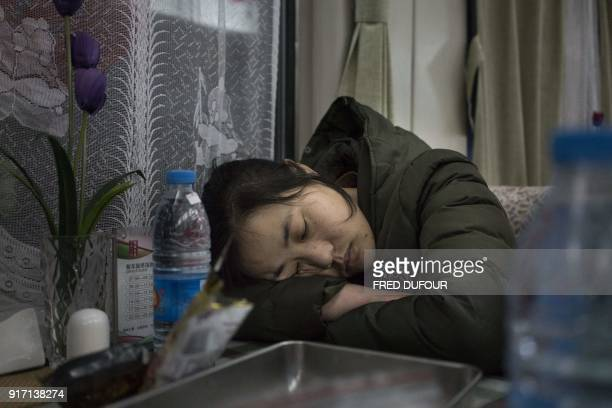This photo taken on February 10 2018 shows people sleeping in the restaurant car during the 26hour train journey from Beijing to Chengdu in Taiyuan...