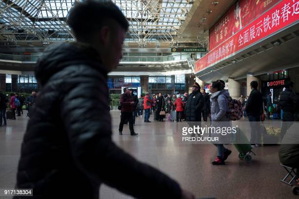 This photo taken on February 10 2018 shows travellers in the main hall at the West Railway Station in Beijing before depart the capital ahead of the...