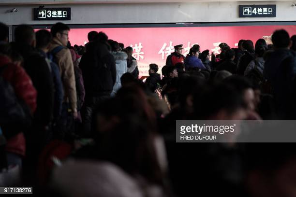 This photo taken on February 10 2018 shows travellers lining up to take their trains at the West Railway Station in Beijing as people depart the...
