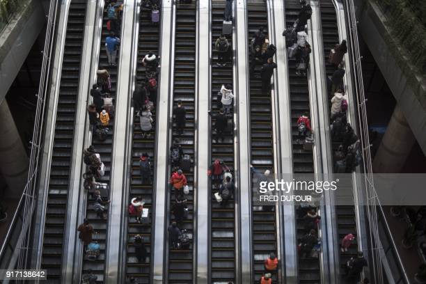 TOPSHOT This photo taken on February 10 2018 shows travellers rushing to the waiting rooms before boarding trains at the West Railway Station in...