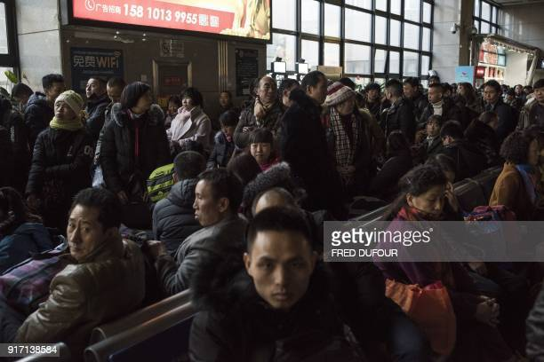 This photo taken on February 10 2018 shows travellers waiting to take their train at the West Railway Station in Beijing as they depart the capital...