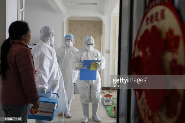 This photo taken on February 10 2020 shows laboratory technicians talking with people during an epidemiological investigation in Linyi in China's...