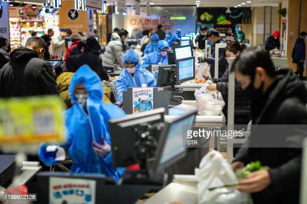 This photo taken on February 10, 2020 shows people wearing protective masks shopping at a super market in Shenyang in China's northeastern Liaoning...