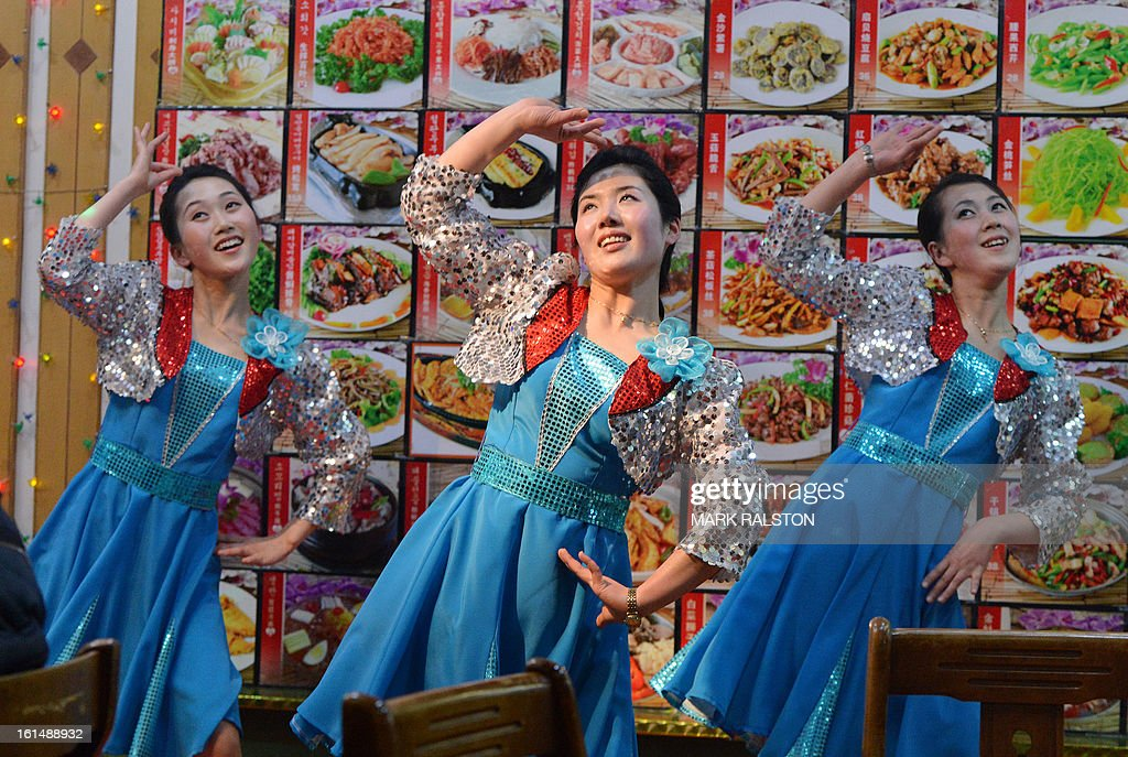 This photo taken on February 11, 2013 shows North Korean waitresses performing in front of a large menu at a North Korean owned restaurant in the Chinese border town of Dandong. North Korean state media outlet has accused the US of 'jumping to conclusions' that the North would soon stage a nuclear test, adding to the confusion over its immediate intentions. The US and its ally South Korea are 'fussing over speculation' without knowing exactly what action the North plans to take, Tongil Sinbo, a Japan-based pro-North weekly magazine funded by Pyongyang, said. AFP PHOTO/Mark RALSTON