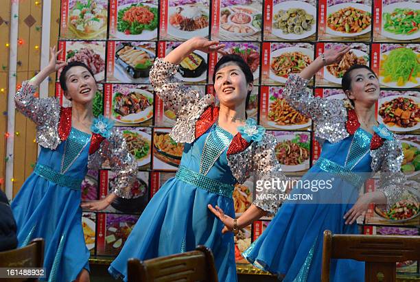 This photo taken on February 11 2013 shows North Korean waitresses performing in front of a large menu at a North Korean owned restaurant in the...