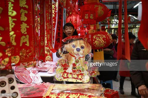 This photo taken on February 11 2018 shows a customer holding a dog decoration at a market in Shenyang in China's northeastern Liaoning province...