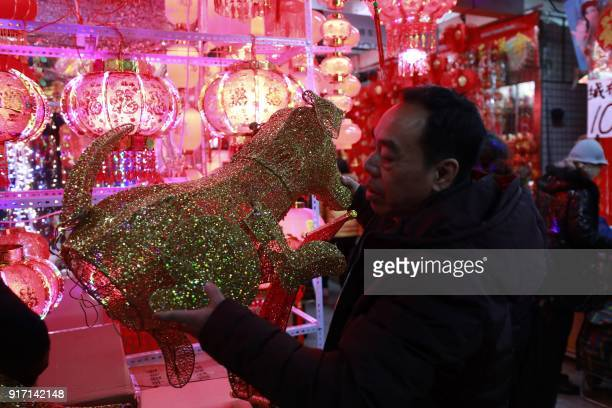This photo taken on February 11 2018 shows a customer holding a dog lantern decoration as he selects items for the upcoming Lunar New Year marking...