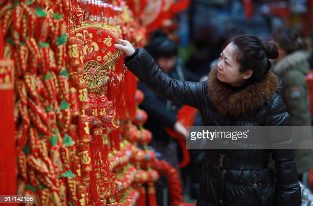 This photo taken on February 11 2018 shows a customer selecting decorations at a market in Shenyang in China's northeastern Liaoning province ahead...
