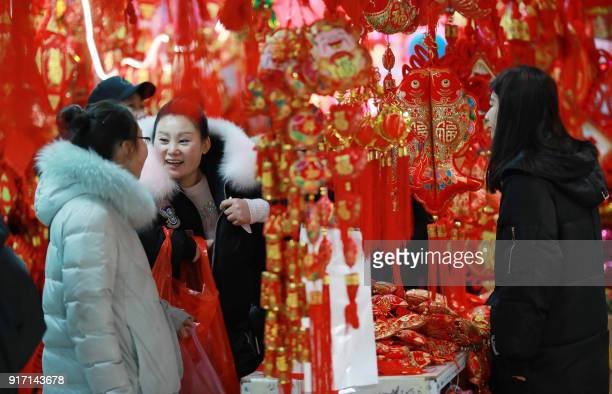 This photo taken on February 11 2018 shows customers buying decorations at a market in Shenyang in China's northeastern Liaoning province ahead of...