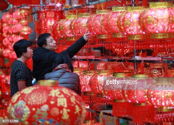 This photo taken on February 11 2018 shows customers selecting lantern decorations at a market in Shenyang in China's northeastern Liaoning province...