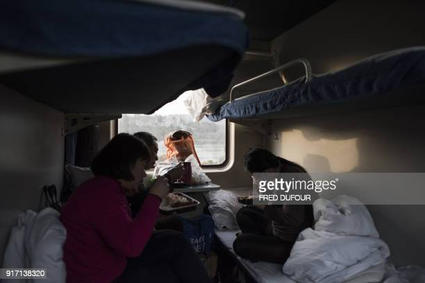 This photo taken on February 11 2018 shows people eating a meal after spending the night on a 26hour train journey from Beijing to Chengdu in...