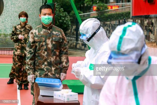 This photo taken on February 11 2020 shows Chinese paramilitary police officers waiting to be tested for the COVID19 coronavirus as they return from...