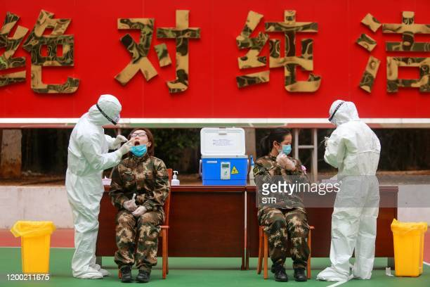 This photo taken on February 11 2020 shows medical staff members collecting samples from Chinese paramilitary police officer to be tested for the...